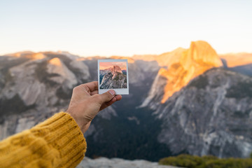 Person with photo near wonderful mountains