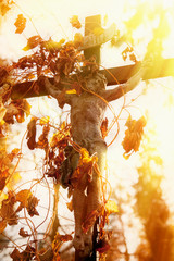 The crucifixion of Jesus Christ with ivy as a symbol of God's love. Antique statue. Religion concept.