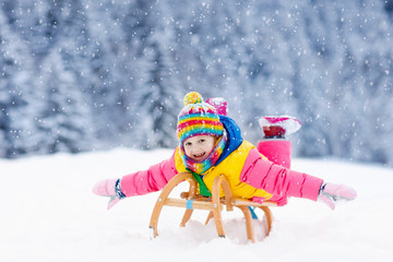 Girl on sleigh ride. Child sledding. Kid with sledge