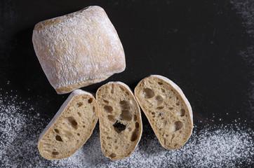 Fototapeta Loaf of ciabatta bread and sliced on a black background obraz