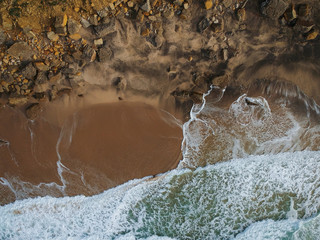 Top view of a beautiful sandy beach aerial shot with the waves rolling into the shore, some rocks present