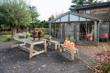 Garden shed in a garden in autumn colors and full of nice decorations