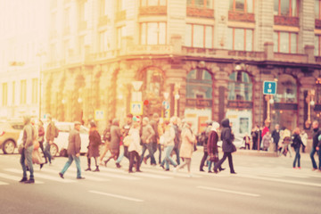 in the blur of the intersection where a group of people cross the street on the background of the building in warm light