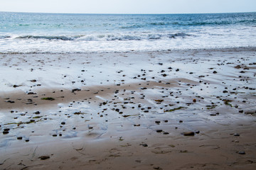 Wet rocky beach sand with many small rocks. Blue ocean with small waves and horizon in the background