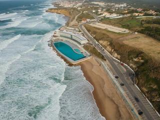"Aerial view of a big sandy beach with waves and a big ocean pool. Portuguese coastline ""Praia Grande"" beach in Sintra. Drone photo"