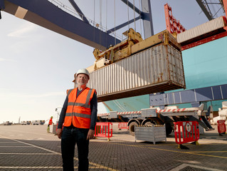 Dock worker by cargo container and truck at Port of Felixstowe, England