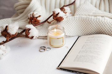objects laid out on the table, an open book and a burning candle