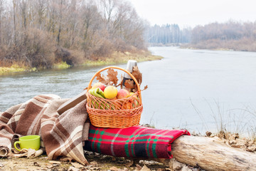 A basket with apples and thermos bottel inside is standing on the colorful blanket at the bank of the autumn river.