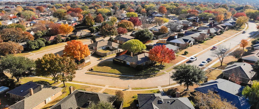 Panorama top view beautiful neighborhood in Coppell, Texas, USA in autumn season. Row of single-family home with attached garage, garden, surrounded by colorful fall foliage leaves under blue sky