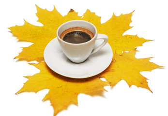 White cup of black coffee with yellow maple leaves on white background, isolated