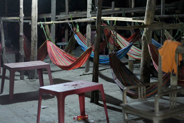 A place to sleep in a barn with hammocks tied to the crossbar between the pillars.