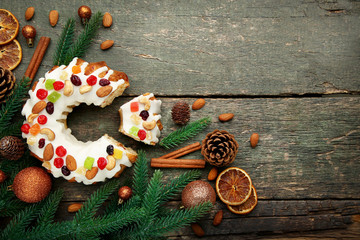 Bundt cake with fir-tree branches and baubles on wooden table