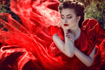 Beautiful young lady with perfect make up and plaited hairstyle wearing luxurious silk red ballroom dress sitting in the poppy field. The wind in her hair. The tail of her dress flying behind