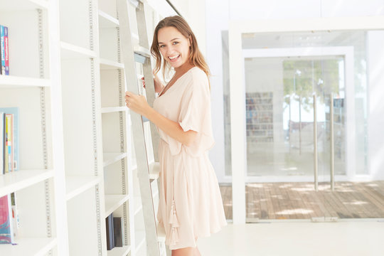 Young woman standing on library ladder
