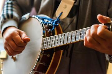 Close up hands of man playing 8-string mandolin