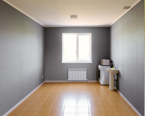 Not equipped empty kitchen room with bright window in new apartment building