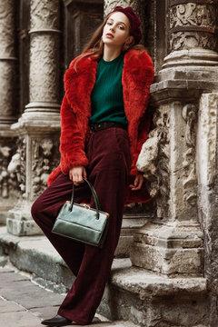 Outdoor full body fashion portrait of young beautiful woman wearing trendy oversized orange faux fur coat, beret, green sweater, corduroy trousers, holding stylish snakeskin bag, posing in street