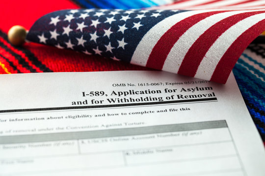Application for asylum to USA concept with application form and USA flag on mexican serape