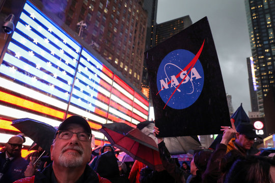 People watch on a video screen as the spaceship InSight lands on Mars surface after a six-month journey, in Times Square in New York