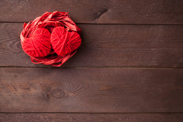 Two red hearts from threads lie in the nest. Sweet romantic background. Valentines day concept. selective focus.