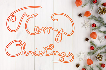 Christmas decorations, pine cones and red balls on a white wooden table. Hand-drawn font. Included Merry Christmas text