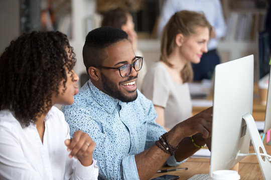 Smiling happy African American man showing funny news to female colleague, looking at screen, employee laughing on workplace, using computer, excited by good result of work