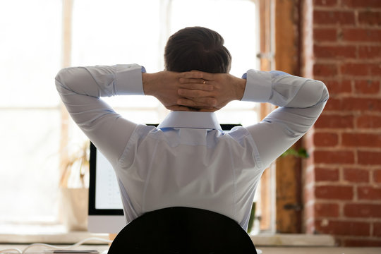 Relaxing businessman stretching with hands behind head after long work in sitting position with computer, sitting in office chair, employee doing simple exercises at workplace, take break