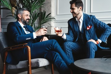 Relaxing. Full length of two young handsome men in suits holding glasses and looking at each other while resting indoors. Wall mural