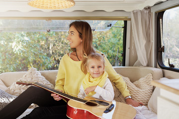 A child of four plays the guitar. Mom smiles and rejoices at her daughter's success