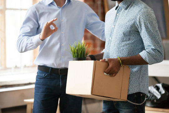Team leader, hr manager, friendly boss, executive introducing new just hired African American employee to colleagues, showing ok symbol, man holding box with belongings, first day at work, close up