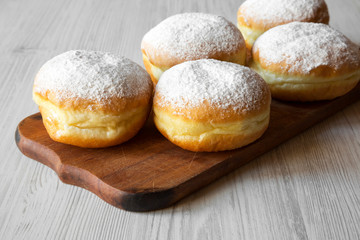 Homemade sweet donuts with powdered sugar on rustic wooden board over white wooden surface, side view. Close-up.