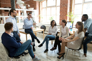 Happy smiling coach, tutor, boss laughing at female employee joke at briefing, colleagues having fun together at company meeting, multiracial staff, team building training, good relationship in team