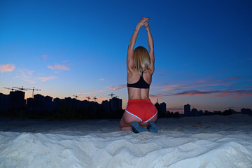 Rear view of sporty girl on her knees in the desert in the evening.