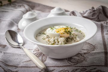 Sorrel soup with egg in white bowl.
