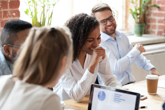 Multiracial group of colleagues having fun at company meeting, briefing, african american businesswoman with coworkers, employees with boss, mentor laughing at funny news, team building