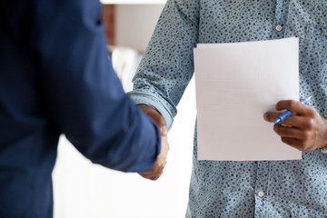 African American businessman, mentor holding paper and shaking hand to employee, trainee, intern, congratulating with good results, greeting, meeting with new office worker, making agreement close up