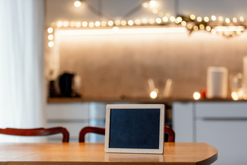 Blackboard on wooden table in kitchen with Christmas fairy lights on background