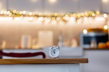little alarm clock on a table with Christmas lights on background. Kitchen interior