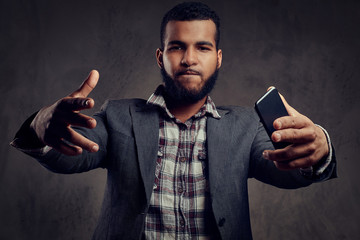 African-American guy is posing next to a dark textured wall.