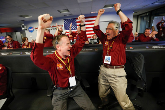 NASA engineers Kris Bruvold and Sandy Krasner react in the space flight operation facility at NASA's Jet Propulsion Laboratory (JPL) as the spaceship InSight lands on the surface of Mars after a six-month journey, at JPL in Pasadena