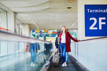 Young woman in international airport with luggage