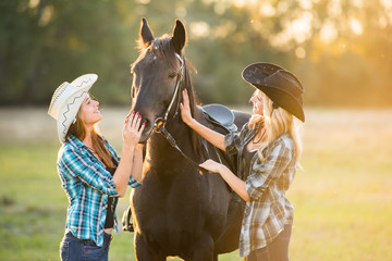 Two girls rider stands near a horse. Horse theme