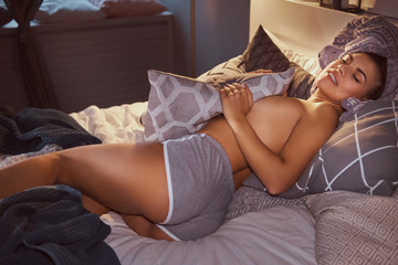 Sexy girl with a towel on her head lying in an embrace with a pillow on the bed.
