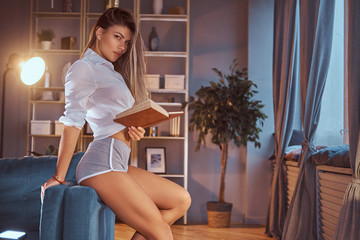 A sexy girl in a translucent blouse without underwear sits on a sofa and holding a book at home, looking at a camera seductively.