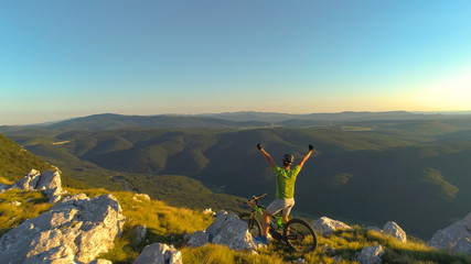 AERIAL: Unrecognizable male backcountry cyclist pumps his fists victoriously.