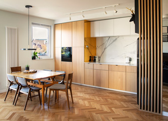 Stylish and cozy scandinavian dining room and kitchen with design family table, chairs and lamp. White walls and brown wooden parquet.