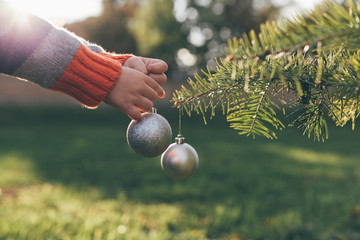 Boy decorating Christmas Tree outdoor
