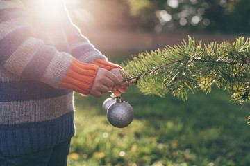 Boy decorating Christmas Tree outdoor
