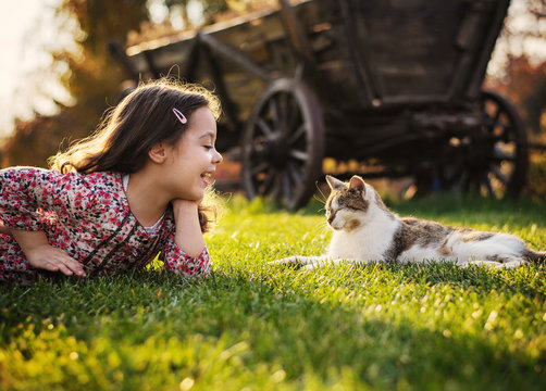 Cute little girl smiling to a cat