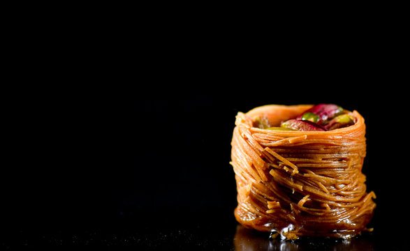 Middle Eastern dessert called mabroume or burma isolated on black background.